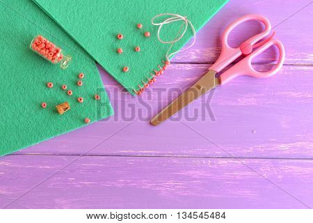 Beaded stitch for a beautiful edging on felt craft projects. How beautifully decorate an edge of fabric product. Green felt sheets, scissors, small glass jar with pink beads on lilac wooden background