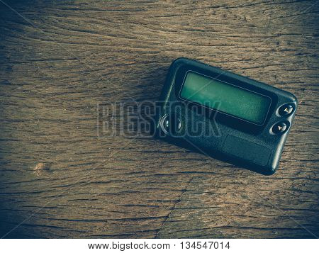 Old pager device on wooden table (vintage or retro tone with lens vignetting effect)