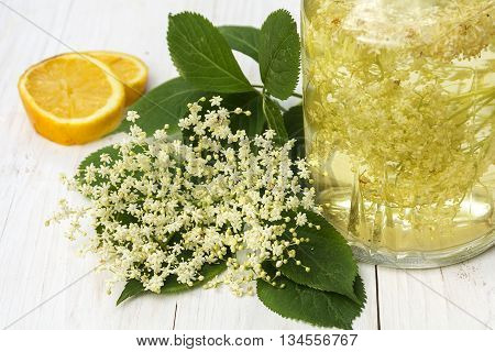 elderflower drink with lemon and sugar in a glass jar on a white wooden table homemade syrup fades for refreshing juice and champagne in summer selective focus narrow depth of field