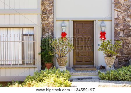 Entrance to the house with a wooden door hanging on the sides of the door red bells with red bow