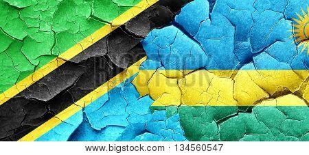 Tanzanian flag with rwanda flag on a grunge cracked wall