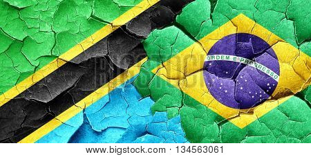 Tanzanian flag with Brazil flag on a grunge cracked wall