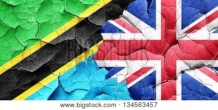 Tanzanian flag with Great Britain flag on a grunge cracked wall