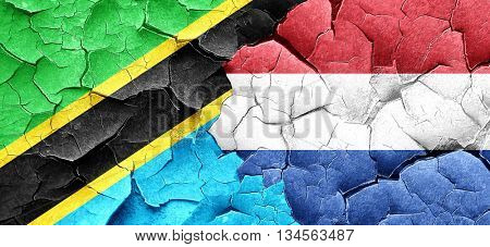 Tanzanian flag with Netherlands flag on a grunge cracked wall