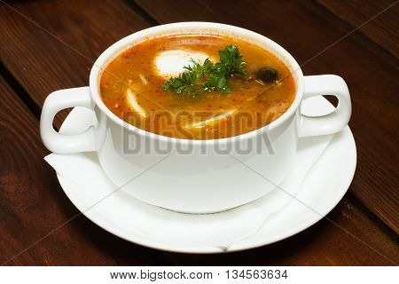 Russian cuisine soup hodgepodge - soljanka on wooden table