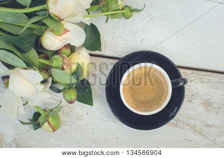 Coffee and flowers peony. A cup of coffee and Peonies on a white wooden table. Breakfast on Mothers day, Valentines Day or Womens day. Spring or summer background. Copy space. Top view. Toned image.