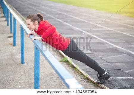 Young woman doing push ups or press ups. Fitness outdoors. Toned image