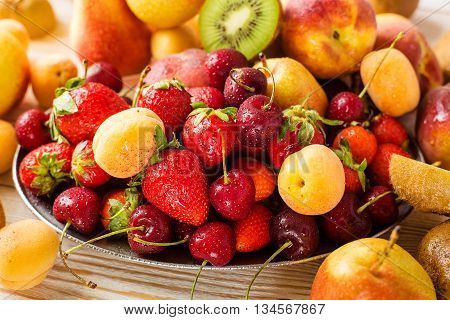 Fresh mixed fruits and berries on plate. Healthy eating, dieting. Summer food, clean eating