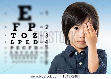 Close up portrait of handsome little asian boy testing eyesight.Kid closing one eye with hand against alphabetical out of focus eye test chart in background.