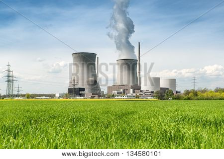 Nuclear power Energy concept - Nuclear power plant with green field and big blue clouds. Nuclear power plant in Germany