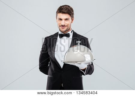 Smiling young butler in tuxedo and gloves holding tray with silver catering dome