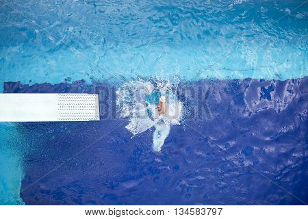 Springboard diver diving into a swimming pool
