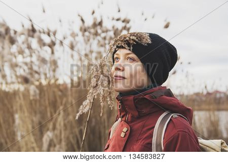 beautiful happy girl near a lake in nature with a cane in his hand, harmonious sensations. traveler girl enjoying life and meditates.