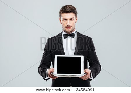 Handsome young butler in tuxedo with bowtie holding blank screen tablet on tray
