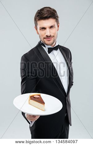 Attractive young butler in tuxedo standing and holding piece of cake on plate