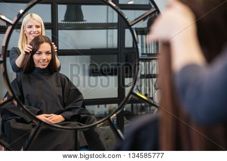 Mirror reflection of young beautiful woman getting her hairdo by stylist at beauty salon