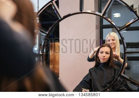 Mirror reflection of young beautiful woman getting her hairdo by stylist at parlor