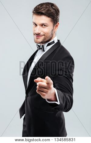 Happy confident young man in tuxedo with bowtie pointing on you
