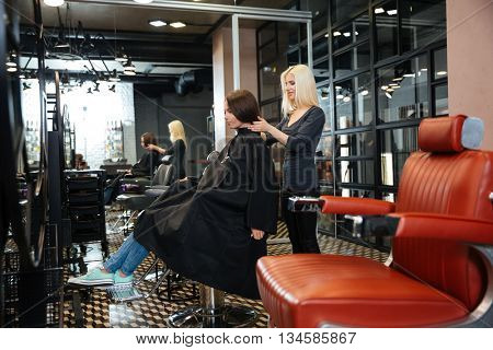 Young girl sitting at the beauty salon and talking with female hairdresser