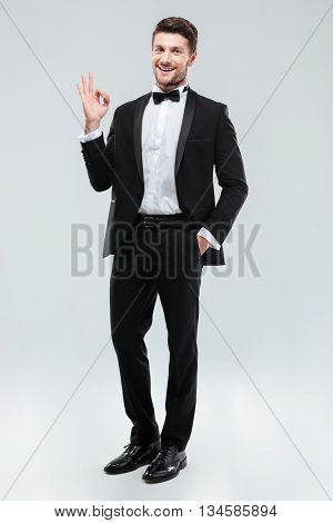 Full length of cheerful young man in tuxedo with bowtie showing ok sign