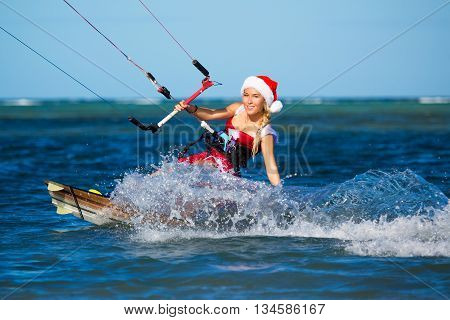 Beautiful young girl on the kite in the costume of Santa Claus. Christmas and New year on a tropical island. Extreme Sport Kitesurfing