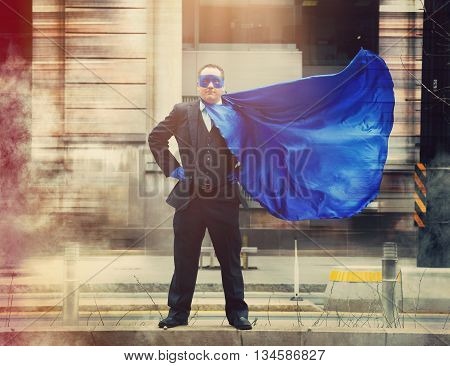 A businessman superhero with a blue cape standing in the city for a determination confidence or success concept.