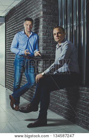 Two Businessmen Are Talking In A Half-dark Corridor.