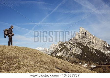 Hiker photographer on a mountain top admiring the surrounding alpine landscape enjoying the view. Active lifestyle natural environment freedom and sports concept. Big blue sky in the background.