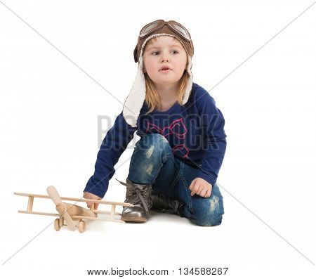 cute little girl in pilot hat with wooden plane in hand isolated on white background