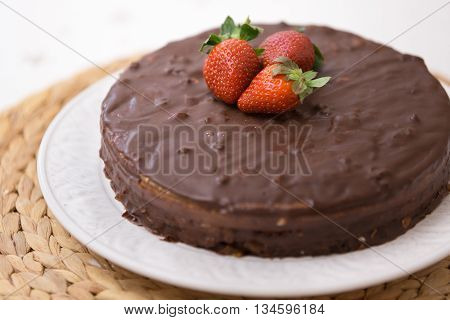 Homemade dark chocolate cake with cocoa and fresh organic strawberries on top served on a white plate and straw tablemat. Delicious party cake fo celebration or holidays.