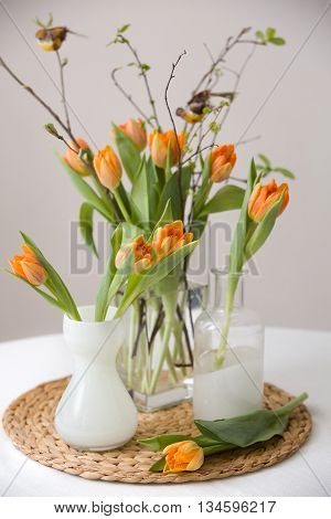 Fresh spring bunch of orange tulips and green leaves and small birds in nice cristal glass vases on the straw board and table with a tablecloth. Home decor for spring and Easter. Beautiful flowers.