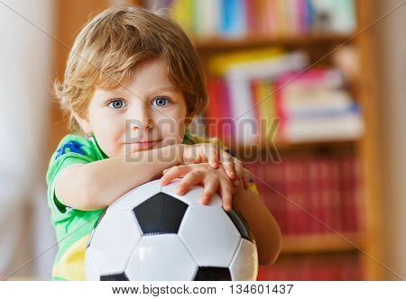 Little blond preschool kid boy of 4 years with football watching soccer cup game on tv. Adorable child enjoying game, fan of his favorite team