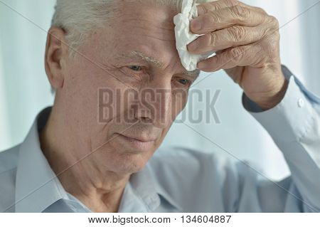 Portrait of an ill senior man suffering from pain