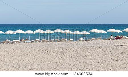Alicante - 12 October 2015: People relax and sunbathe on the Mediterranean Sea under the white beach umbrella on shizlongah and white sand long beach Alicante Costa Blanca October 12 2015 Alicante Spain