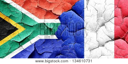 South africa flag with France flag on a grunge cracked wall
