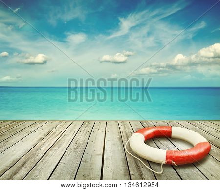 Wood pier with ocean and life preserver and blue sky in background