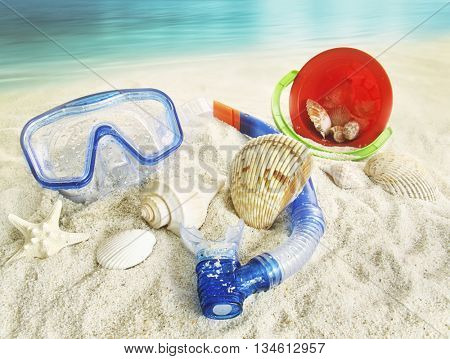 Water goggles and beach toys in the sand
