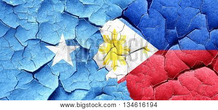 Somalia flag with Philippines flag on a grunge cracked wall