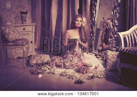 Stylish woman in a vintage dress in a luxurious interior. Fashion girl in a retro way. Portrait of a model in a vintage hat. The image of the last century