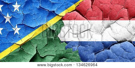 Solomon islands flag with Netherlands flag on a grunge cracked w