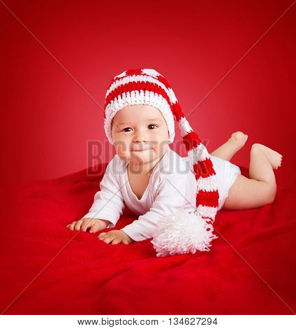 little baby in knitted red whitey hat on red blanket