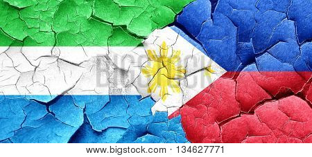 Sierra Leone flag with Philippines flag on a grunge cracked wall