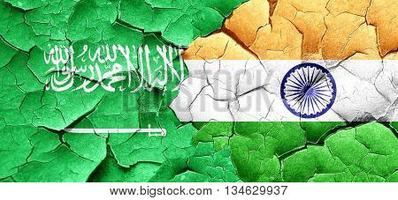 Saudi Arabia flag with India flag on a grunge cracked wall