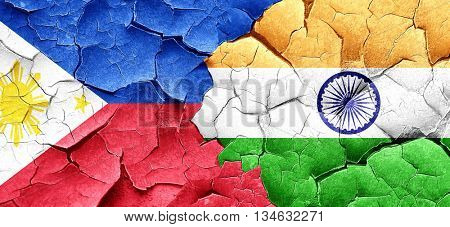 Philippines flag with India flag on a grunge cracked wall