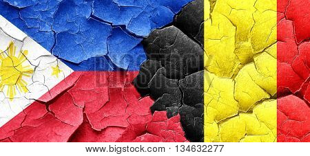 Philippines flag with Belgium flag on a grunge cracked wall