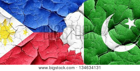 Philippines flag with Pakistan flag on a grunge cracked wall
