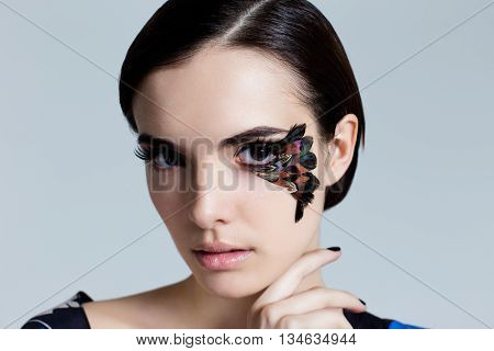 Portrait of pretty woman face with false feather eyelashes fashion makeup