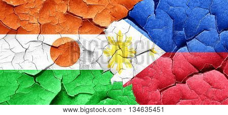 niger flag with Philippines flag on a grunge cracked wall