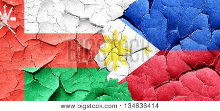 Oman flag with Philippines flag on a grunge cracked wall