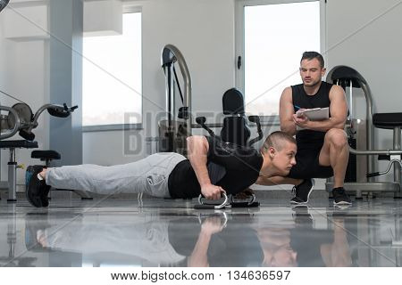 Young Man With Personal Trainer Exercise Push-up